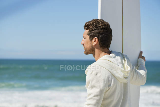 Man holding surfboard at wavy sea and looking away — Stock Photo