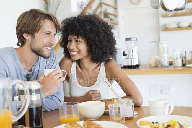 Couple sitting at dining table and having breakfast — Stockfoto