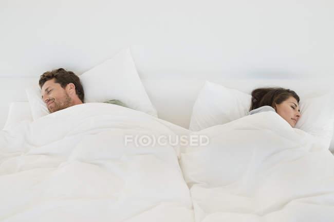 Coppia che dorme sul letto con biancheria bianca — Foto stock