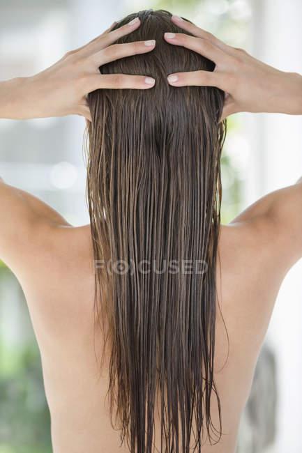 Vista posteriore della donna massaggio bagnato capelli lunghi — Foto stock