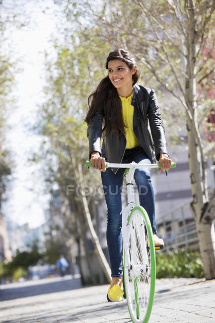 Smiling young woman riding bicycle outdoors — Stock Photo