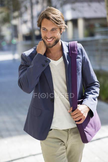 Молодой человек ходит по улице и улыбается — стоковое фото