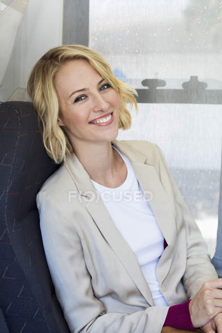 Portrait of smiling blonde woman sitting in armchair — Stock Photo