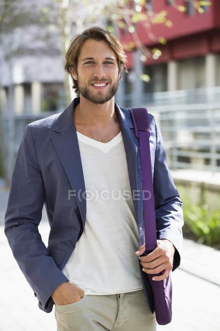 Портрет молодого человека, идущего по улице и улыбающегося — стоковое фото