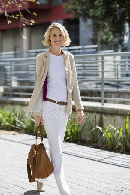 Ritratto di donna sorridente fiduciosa a piedi sulla strada e rivolto verso l'obiettivo — Foto stock
