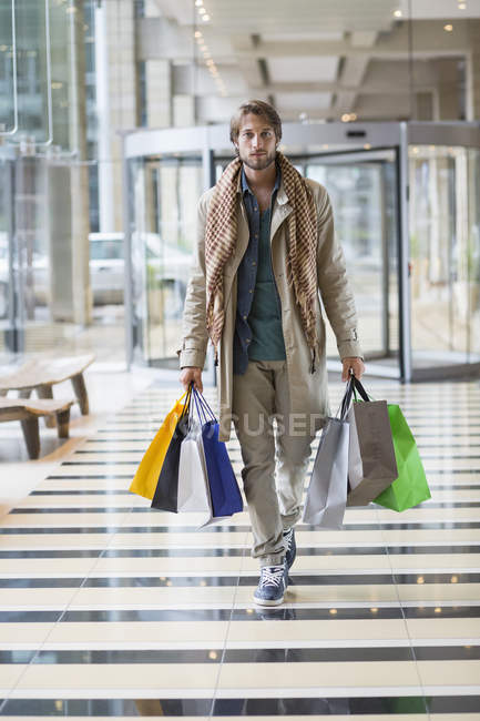 Portrait of young elegant man carrying shopping bags — Stock Photo