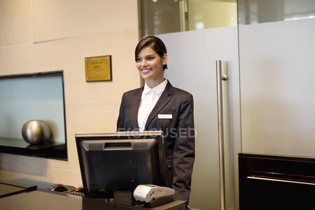 Recepcionista femenina de pie en el mostrador de recepción del hotel y sonriendo - foto de stock