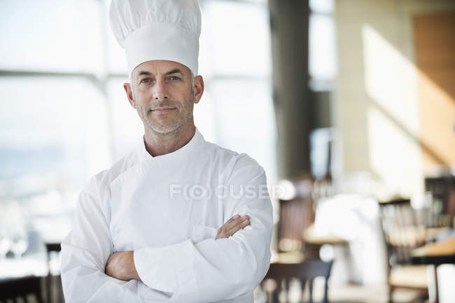 Portrait of confident male chef with arms crossed in restaurant — Stock Photo