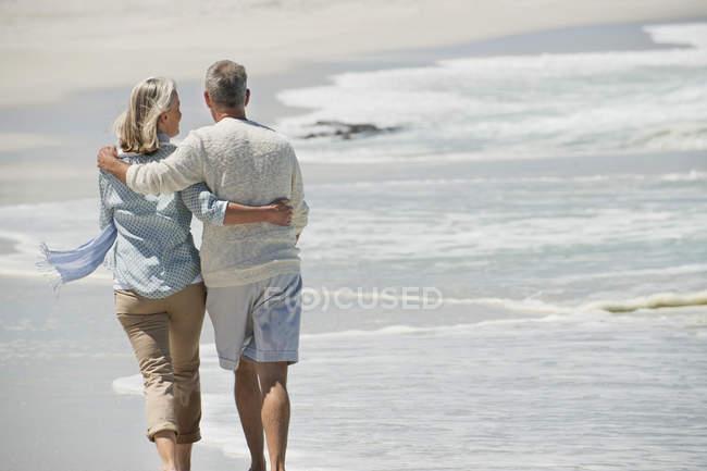 Вид сзади на романтическую пожилую пару, гуляющую по пляжу — стоковое фото