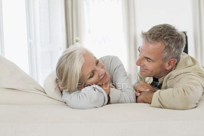 Romántica pareja senior descansando en la cama y mirando el uno al otro - foto de stock