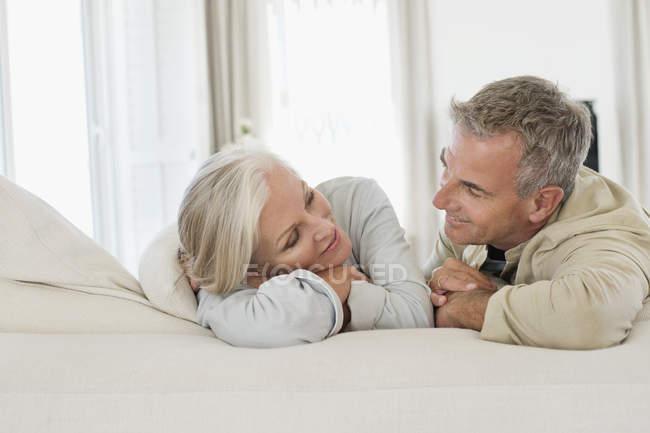 Romantisches Seniorenpaar, das sich auf dem Bett ausruht und einander ansieht — Stockfoto