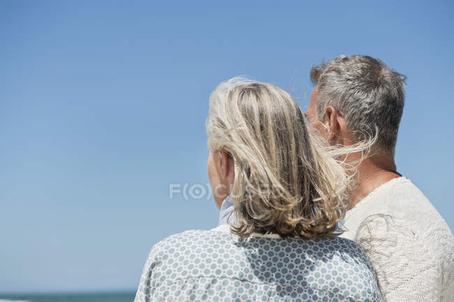 Romantic senior couple standing on against clear blue sky — Stock Photo
