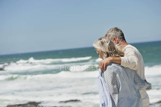 Embracing senior couple walking on sea beach — Stock Photo