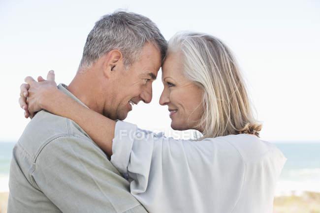 Романтическая старшая пара, обнимающаяся на открытом воздухе — стоковое фото