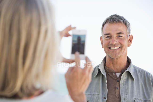 Mulher tirando foto de marido com celular na praia — Fotografia de Stock