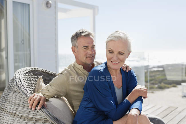 Romantic senior couple sitting in wicker chair outdoors — Stock Photo