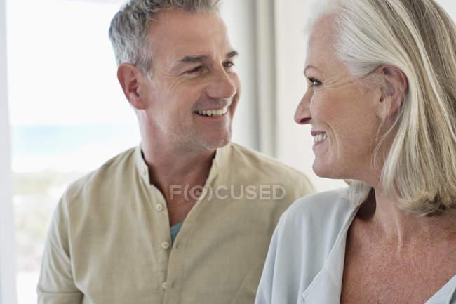 Крупным планом улыбающейся пожилой пары, смотрящей друг на друга — стоковое фото