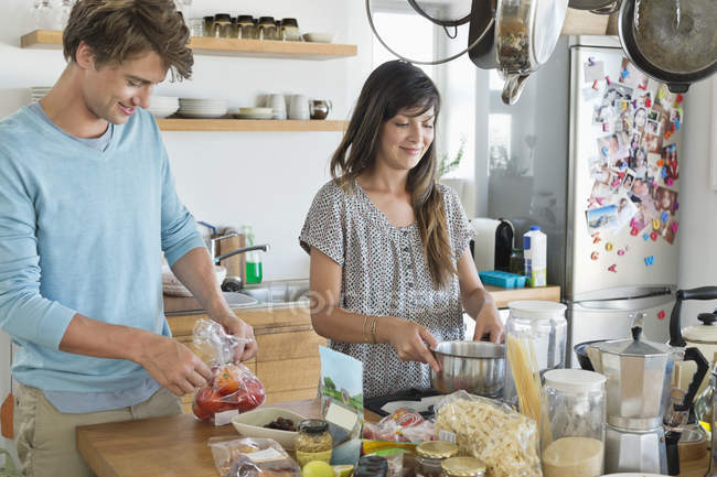 Smiling young couple cooking in kitchen — Stock Photo