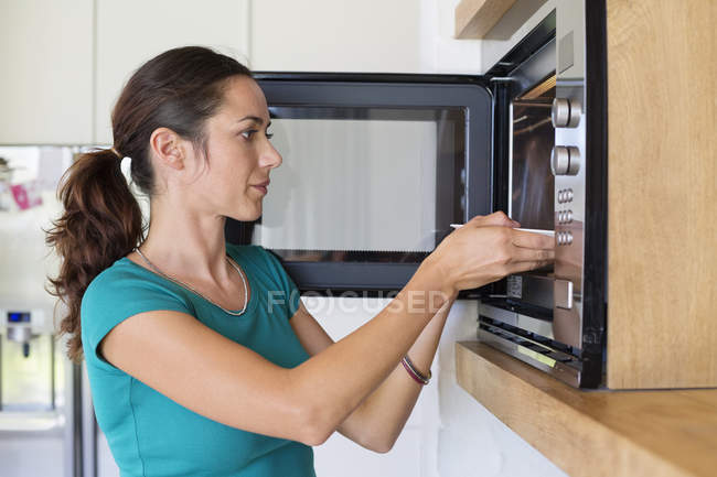 Woman putting food into oven in modern kitchen — Stock Photo