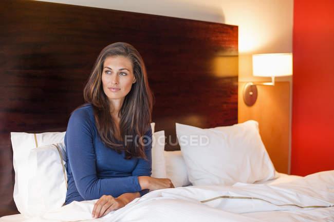 Porträt einer lächelnden Frau auf dem Bett im Hotelzimmer — Stockfoto