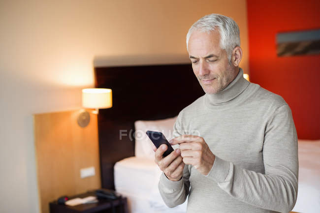 Man using a mobile phone in a hotel room — Stock Photo
