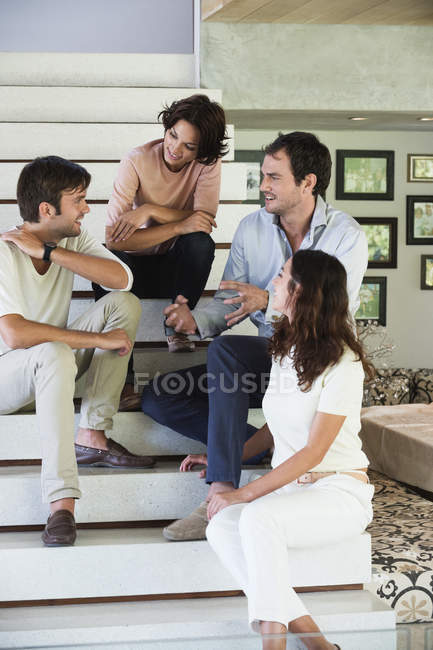 Smiling friends sitting on steps and talking — Stock Photo