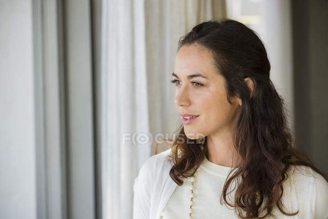 Close-up of smiling woman standing at home and looking away — Stock Photo