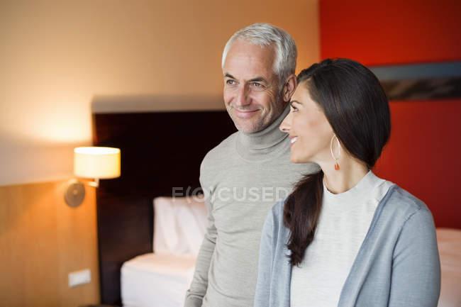 Улыбающаяся пара, стоящая вместе в номере отеля — стоковое фото
