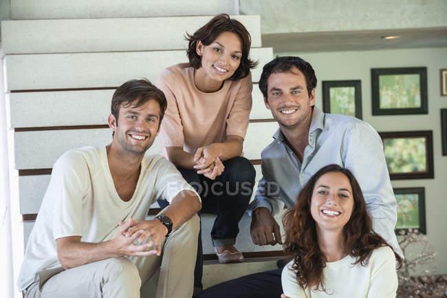 Портрет улыбающихся друзей, сидящих на ступеньках — стоковое фото
