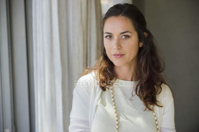 Портрет молодой элегантной женщины, стоящей у занавеса в комнате — стоковое фото