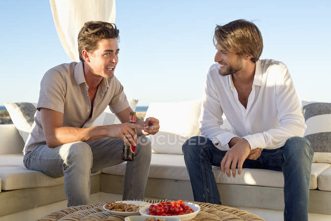 Male friends talking while sitting on sofa on resort — Stock Photo