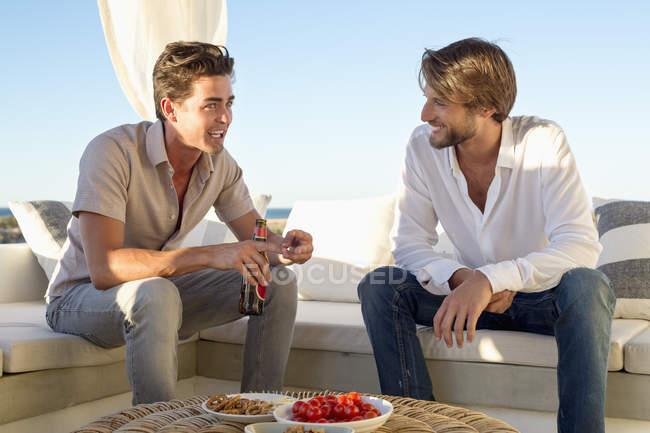 Masculino amigos falando enquanto sentado no sofá no resort — Fotografia de Stock