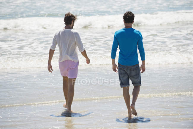 Relaxed men walking on beach with wavy sea — Stock Photo