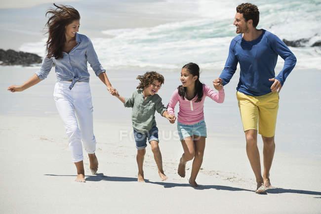 Familia feliz caminando en la playa de arena de la mano - foto de stock