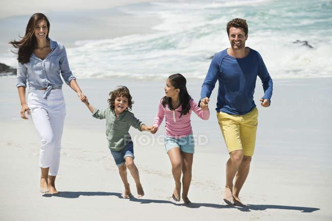Счастливая семья, гуляющая по песчаному пляжу, держась за руки — стоковое фото