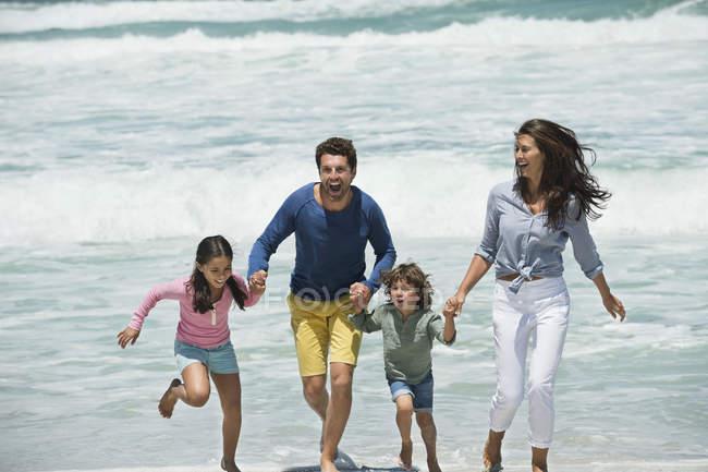 Famille heureuse courir sur la plage avec la mer ondulante — Photo de stock