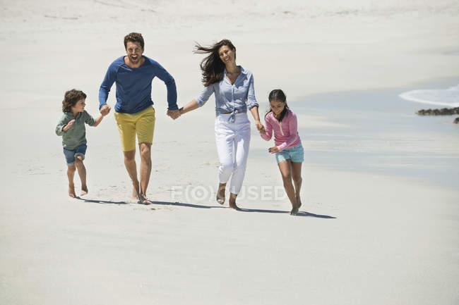 Glückliche Familie läuft am Sandstrand — Stockfoto