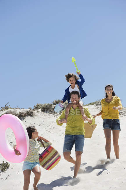 Happy family walking on sandy beach in summer — Stock Photo