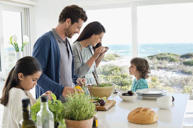 Happy family preparing food in coastal house — Stock Photo