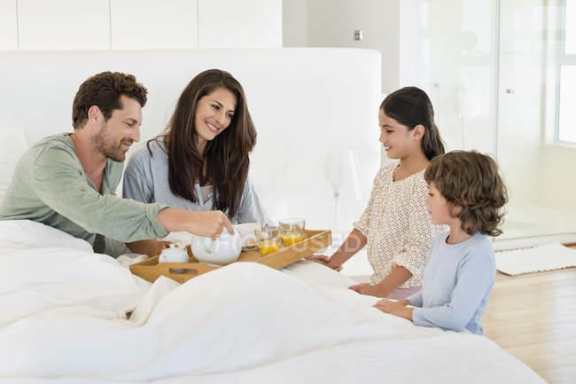 Niños sirviendo té a padres felices en la cama - foto de stock