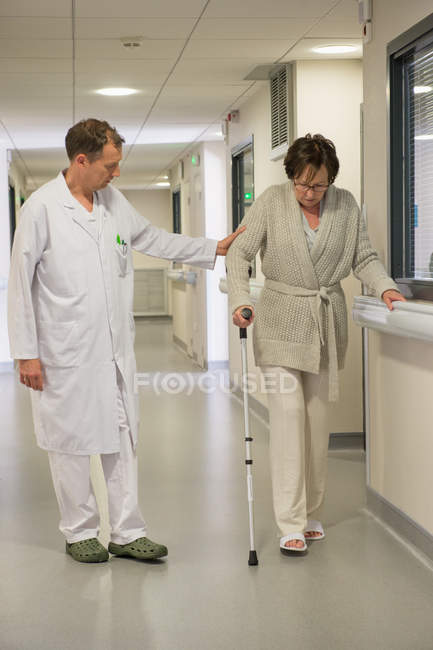 Male doctor assisting female patient on crutches in hospital — Foto stock