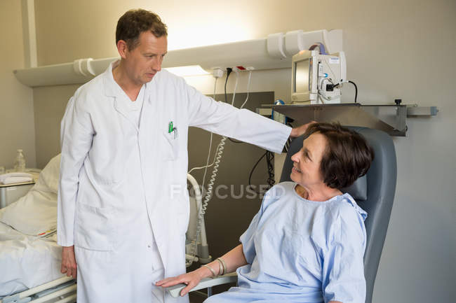 Male doctor assisting female patient in hospital — Stock Photo