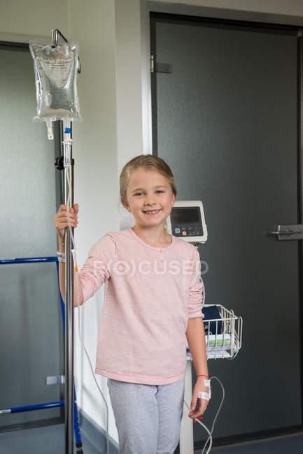 Retrato de niña rubia sonriente paciente de pie en el hospital con goteo iv - foto de stock