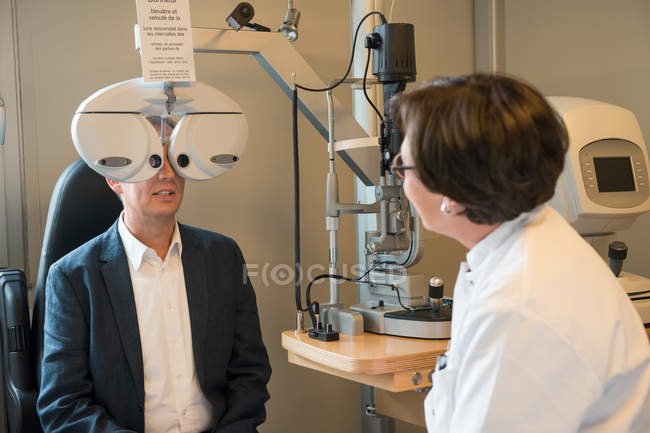 Female optometrist examining male eyes — стоковое фото