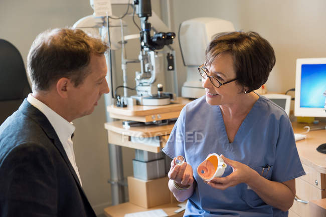 Female optometrist discussing with patient in a clinic — Foto stock