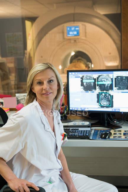 Retrato de mujer médico examen de resonancia magnética cerebral en computadora - foto de stock