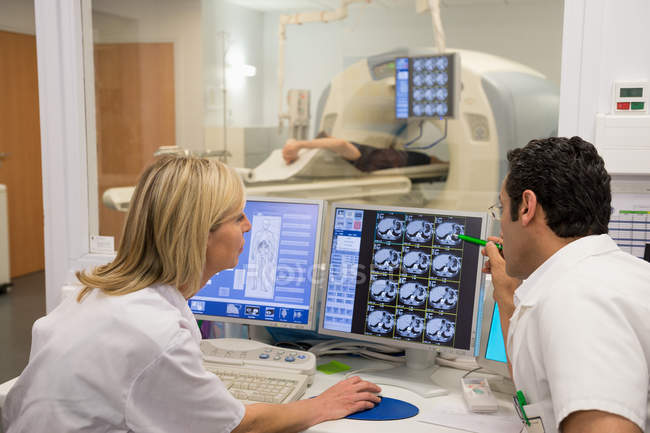Doctors examining scan on computer with patient on MRI scanner in background — Stock Photo