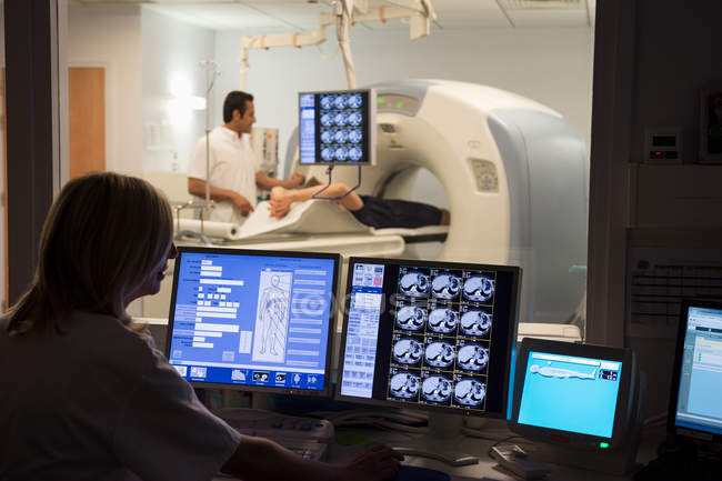 Female doctor examining scan on computer with patient on MRI scanner in background — Stock Photo