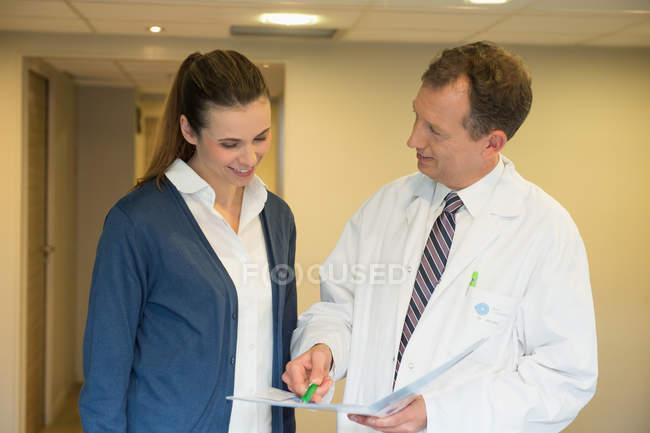 Врач-мужчина обсуждает медицинское заключение с женщиной в больнице — стоковое фото