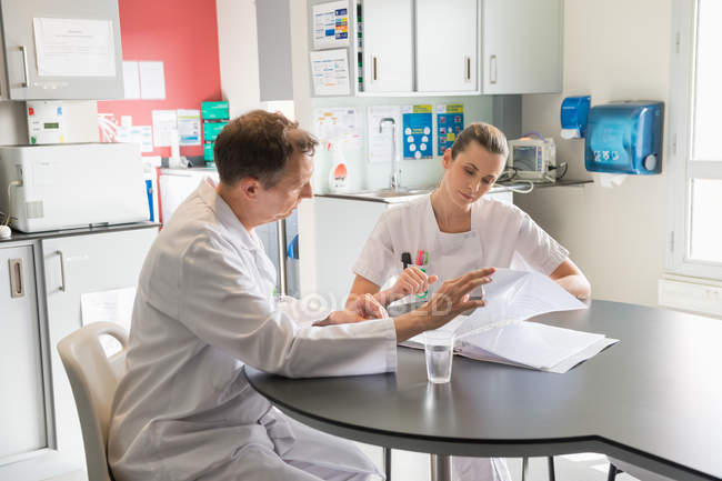 Doctor and nurse analyzing medical record in a hospital — Stock Photo